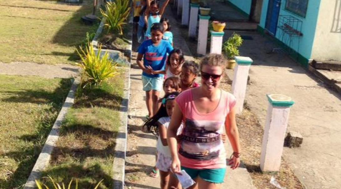 Projects Abroad volunteer working with children in Philippines leads school children outside their kindergarten at her Childcare Project.